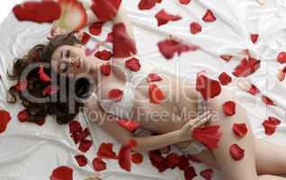 Sexy underwear model posing lying in rose petals