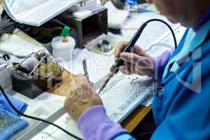 Manufacturing. Worker soldering circuit board