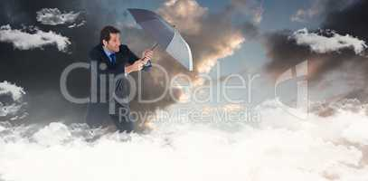 Composite image of man holding umbrella to protect himself from