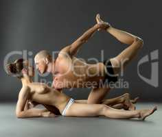 Sexual yoga workout. Topless woman and her trainer