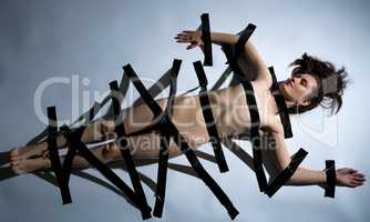 Concept. Naked body of girl covered with duct tape