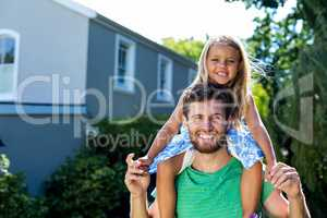 Father carrying daughter on shoulders in yard