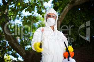 Man spraying insecticide while standing against tree
