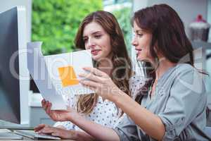 Two woman looking at document and using computer