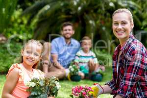 Smiling mother and daughter with flower pots in yard