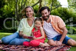 Smiling family with mobile phone sitting in yard