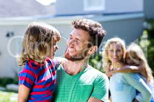 Parent carrying children in yard