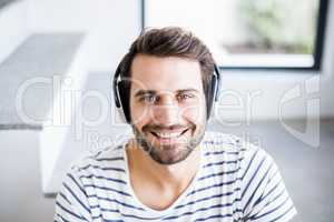 Portrait of happy man listening to music on headphone
