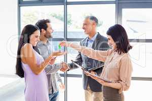 Real estate agent handing over house key to young couple