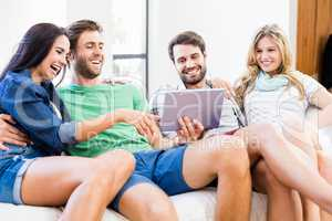 Friends are smiling and looking at a touchscreen