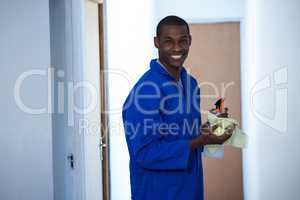 Happy handyman holding spraying insecticide and napkin