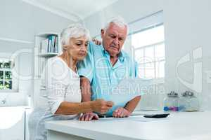 Senior couple calculating finances at home