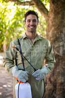 Portrait of happy worker with insecticide sprayer