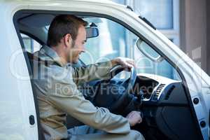 Delivery man starting a car
