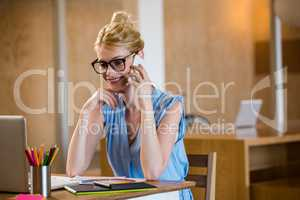 Graphic designer in office sitting at desk and talking on mobile