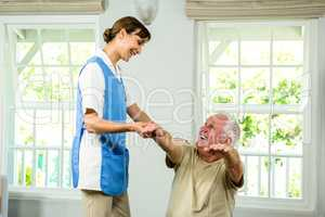 Happy nurse and senior man at health club