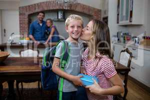 Mother kissing his son while giving him a school lunch box