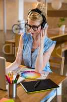 Graphic designer listening to headphones while using laptop