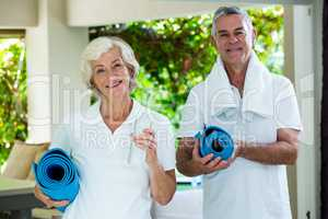 Happy senior couple holding exercise mats