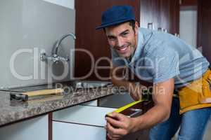 Smiling man measuring drawer size