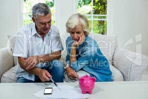 Senior man discussing with wife regarding savings on sofa