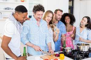 Friends having alcoholic beverage and preparing meal in kitchen