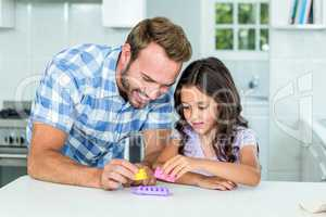 Father and daughter playing with toy block at table