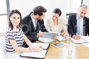 Workers are looking at their notes and one of them are smiling a