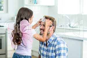 Daughter in angel costume putting crown on father head