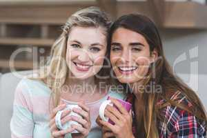 Two beautiful women sitting side by side with a mug of coffee