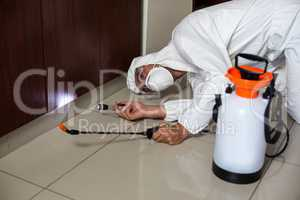 Worker using flashlight under cabinet