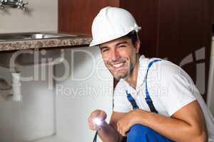 Portrait of smiling man holding illuminated torch