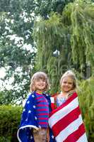 Portrait of siblings wrapped in American flag at back yard