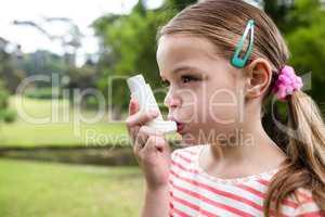 Girl using an asthma inhaler