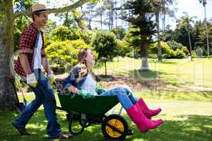 Happy couple playing with a wheelbarrow