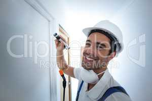 Portrait of happy worker using flashlight