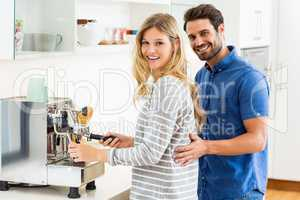 Young couple preparing coffee from coffeemaker