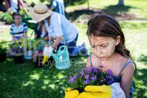 Girl holding a flower pot while gardening with family
