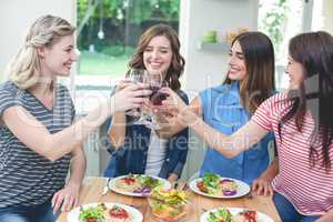 Friends toasting glass of red wine while having meal