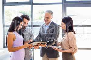 Real estate agent handing over agreement paper to couple