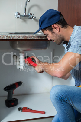 Man using pipe wrench while fixing sink pipe