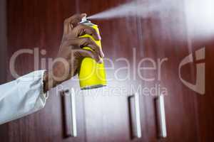Hand spraying pesticide from a spray can
