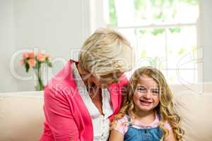 Smiling granny and girl sitting on sofa