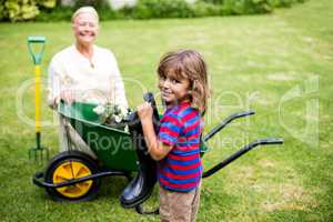 Boy holding wellington boots besides granny in yard