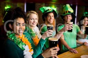 Smiling friends with Irish accessory