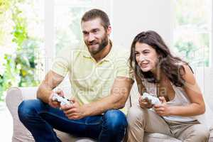 Young couple sitting on sofa and playing video game in living ro