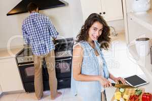 Woman chopping vegetables and man cooking on stove