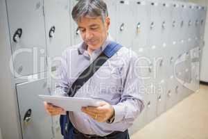 Professor using digital tablet in locker room