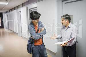 Professor with notebook talking to student