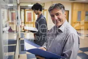 Portrait of smiling professor standing in front of notice board
